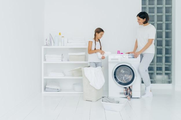 Innenschuß der glücklichen mutter und der tochter stehen nahe waschmaschine, mädchen gießt flüssiges pulver, lastwaschmaschine mit schmutziger kleidung, tut hausarbeit, hat wäschereitag zu hause. hausarbeit-konzept