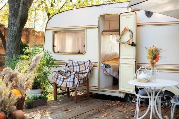 Innensommerterrasse mit blumen in töpfen und einem tisch und stühlen auf der hausveranda mit einem wohnwagen