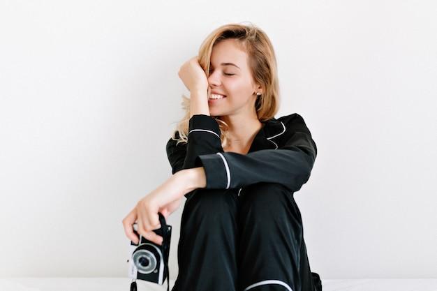 Innenstudioaufnahme der reizenden glücklichen frau schloss augen und smiing, während auf dem bett über weißer wand mit retro-kamera sitzend