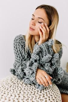 Innenstudioaufnahme der reizenden sinnlichen frau mit den blonden haaren und den geschlossenen augen, die ihr gesicht berührend strickpullover berühren, der im weißen raum posiert