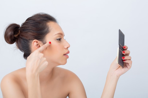 Innenstudioaufnahme der schönen asiatischen frau lächelnd, die lidschattenpalette mit natur-make-up anwendet