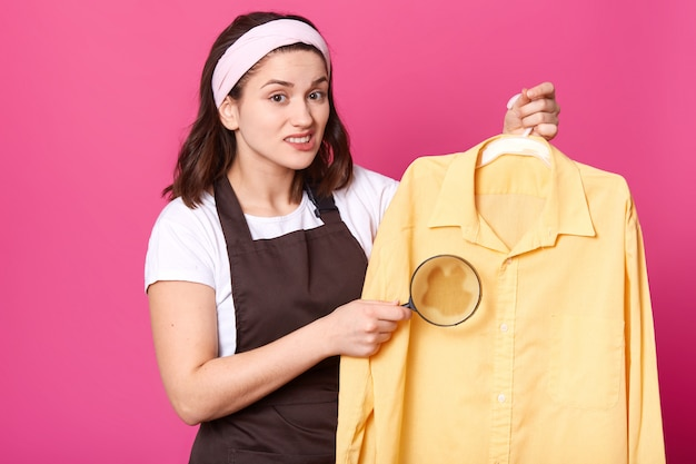 Innenstudioaufnahme der schwarzhaarigen emotionalen niedlichen jungen frau, die lupe in einer hand und hellgelbes hemd auf kleiderbügel hält, kaffeefleck auf kleidern, unzufrieden mit den ergebnissen des waschens.