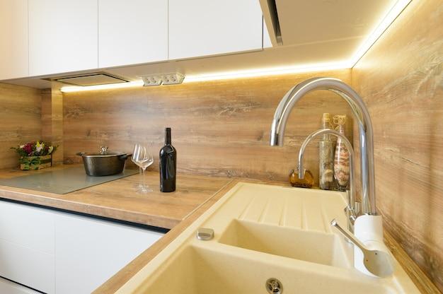 Innere details der modernen weißen und beigen hölzernen küchenküche