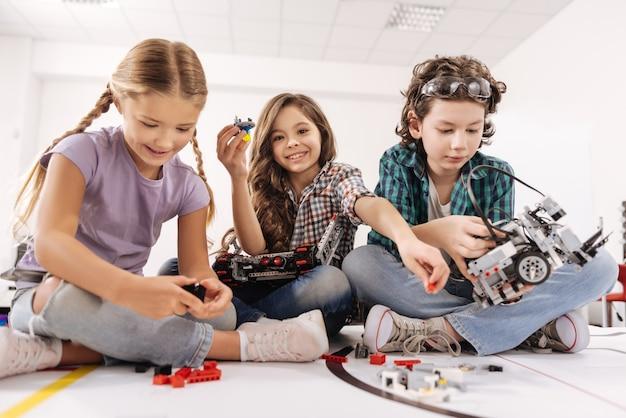 Innovatives bildungssystem. freudige, glückliche, aufrichtige kinder, die im klassenzimmer sitzen und mit geräten und geräten spielen, während sie interesse bekunden