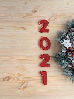 Inschrift 2021 auf hölzernem hintergrund. weihnachtshintergrund. weihnachtsmuster. vertikaler rahmen.