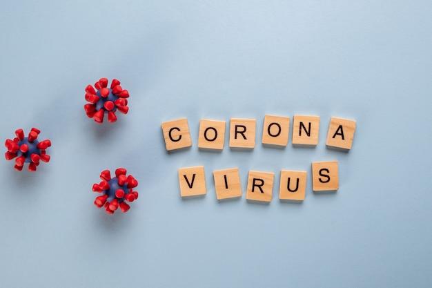 Inschrift coronavirus bestehend aus holzbuchstaben und modellen des covid-19-virus. virus-pandemie-schutz-konzept