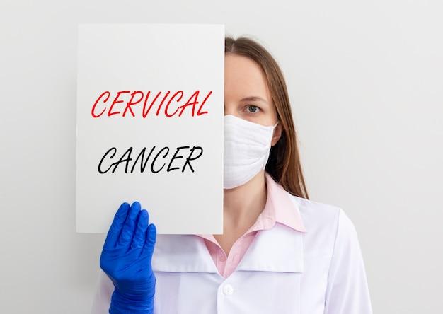 Inschrift der gebärmutterhalskrebskrankheit auf papier in arzthänden in handschuhen, weibliche onkologie.