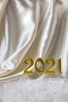Inschrift der goldenen zahlen 2021 auf hintergrund beiger seidenfaldas, vertikale ausrichtung