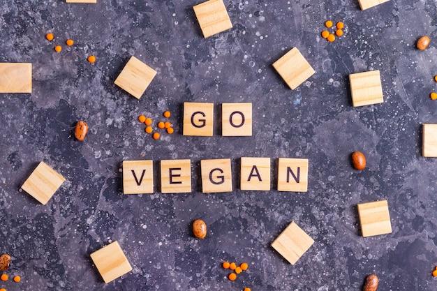 Inschrift gehen vegan in holzbuchstaben mit rohen bohnen und orange linsen auf einem grauen betonhintergrund