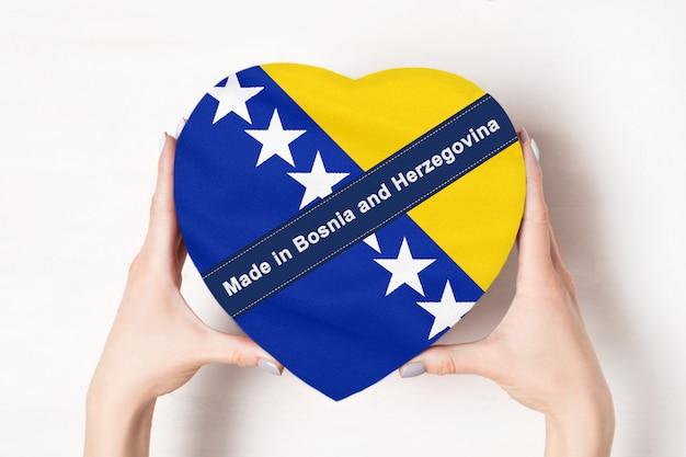 Inschrift hergestellt in bosnien und herzegowina die flagge von bosnien und herzegowina. weibliche hände, die eine herzförmige box halten. weiße wand.