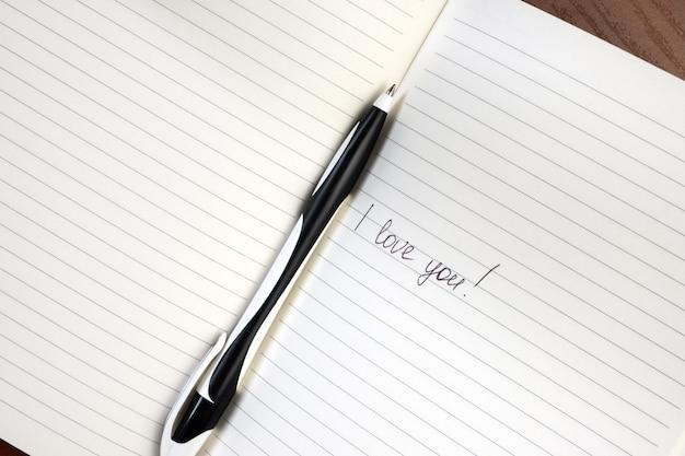 Inschrift ich liebe dich geschrieben auf liniertem notizblock