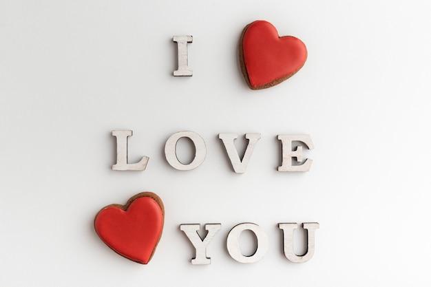 Inschrift ich liebe dich und roter herzförmiger lebkuchen, weißer hintergrund. valentinstag.