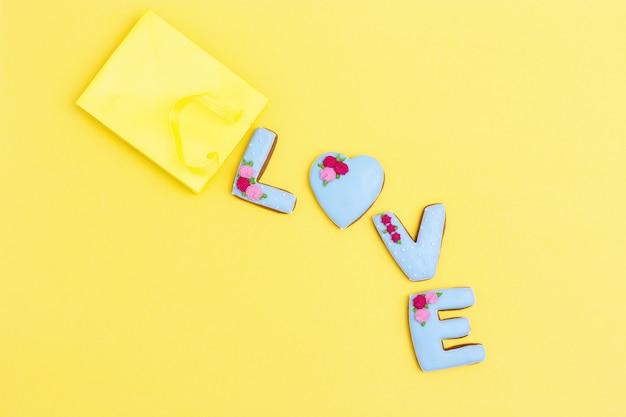 Inschrift liebe durch hausgemachte kekse mit blauem zuckerguss auf gelb
