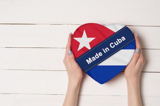 Inschrift made in cuba, die flagge kubas. weibliche hände, die einen geformten kasten des herzens halten.