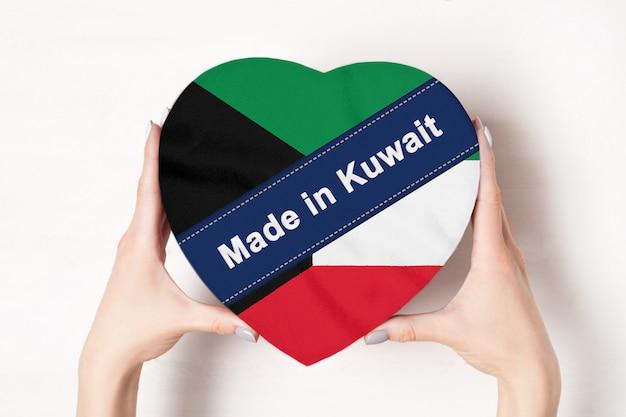 Inschrift made in kuwait, die flagge von kuwait. weibliche hände, die einen geformten kasten des herzens halten.