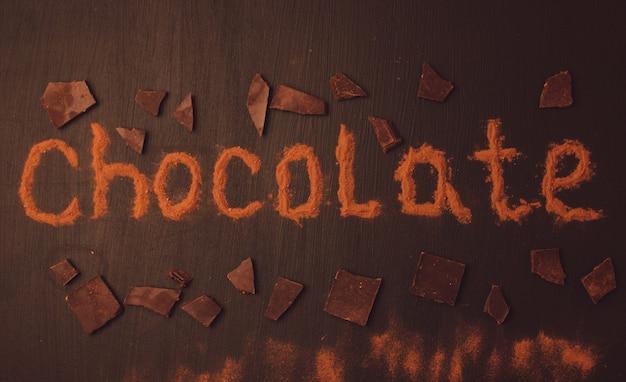 Inschrift schokolade mit kakaopulver mit der zugabe von schokoladenstücken gemacht