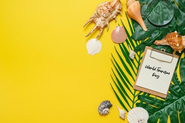 Inschrift zum welttourismustag auf gelbem hintergrund, mit palmblättern, muschelschale und schuhen flach hintergrund