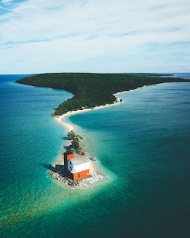 Insel bedeckt im grünen, umgeben vom meer mit einem kleinen haus unter einem bewölkten himmel