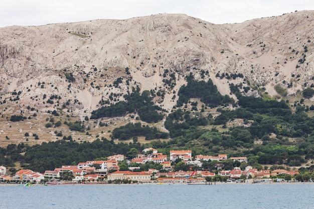 Insel kroatien anzeigen. landschaft traditionelle kroatische stadt mit orange dächern. berge im hintergrund. wolkiges wetter. ufer der adria.