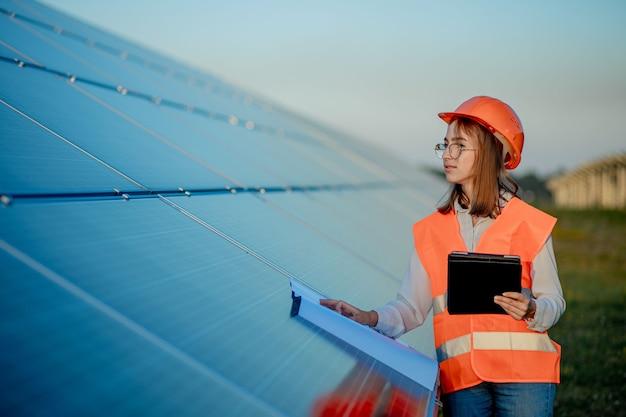 Inspector engineer woman holding digital tablet arbeiten in solar panels power farm
