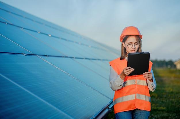 Inspector engineer woman holding digital tablet arbeiten in solarmodulen power farm, photovoltaik-zellpark, green energy concept.