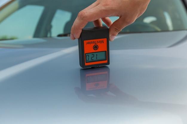 Inspektion der karosserie und motorhaube des autos der mann vermisst die karosserie des autos mit dem gerät