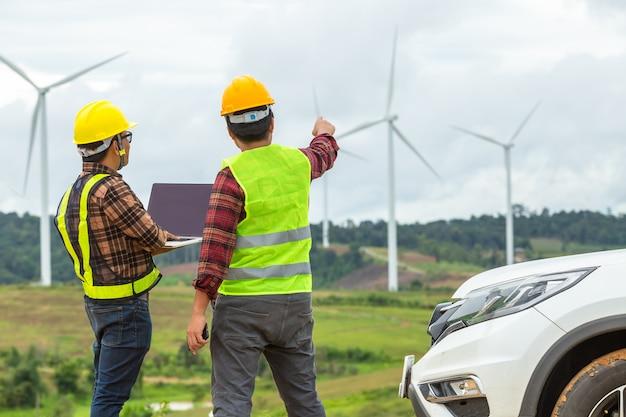 Inspektion mit zwei windmühleningenieuren und fortschritt überprüfen windkraftanlage an der baustelle, indem sie ein auto als fahrzeug verwenden.
