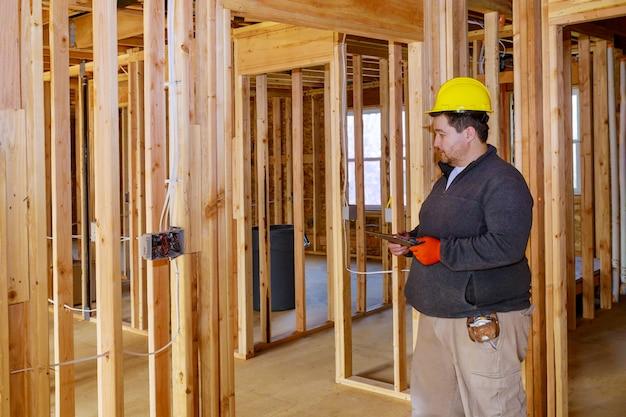 Inspektor mit gelbem schutzhelm, der die elektrische verkabelung im haus überprüft