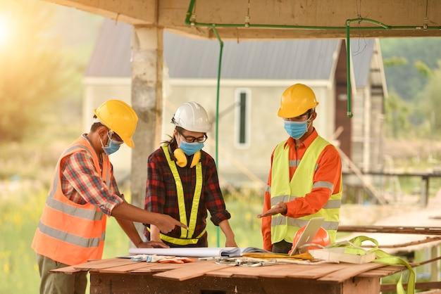Inspektorinnen und architekten diskutieren mit dem chefingenieur über das bauprojekt. eine multiethnische gruppe von ingenieuren trifft sich am vorabend auf der baustelle