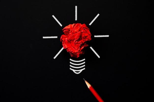 Inspiration und großartige idee konzept. glühlampe mit zerknittertem buntem papier und rotem bleistift