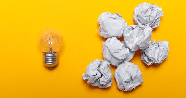 Inspirationskonzept zerknittertes papier und glühbirnenmetapher für gute idee. weißes zerknittertes papier und glühbirne auf gelbem hintergrund, flach liegen.