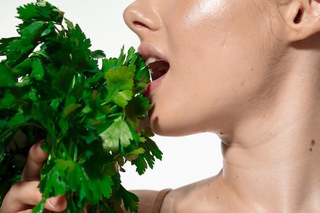 Inspiriert. schließen sie oben von der schönen jungen frau mit den grünen blättern auf ihrem gesicht über weiß. kosmetik und make-up, natur- und umweltbehandlung, hautpflege