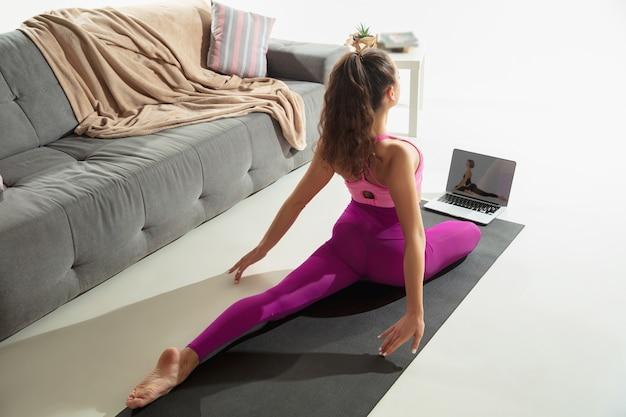 Inspiriert. schöne junge frau, die drinnen arbeitet, yoga-übung auf grauer matte zu hause machend. langes haar fit kaukasischen modell üben. konzept des gesunden lebensstils, der geistigen, der achtsamkeit, des gleichgewichts.