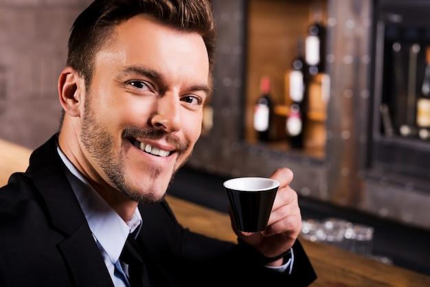 Inspiriert von einer tasse frischen kaffees. selbstbewusster junger mann in abendkleidung, der kaffee trinkt und lächelt, während er an der bartheke sitzt