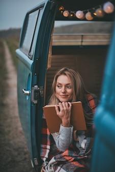 Inspiriert von ihrem buch ... attraktive junge frau, bedeckt mit einer decke, die wegschaut und lächelt, während sie in dem blauen minivan im retro-stil sitzt