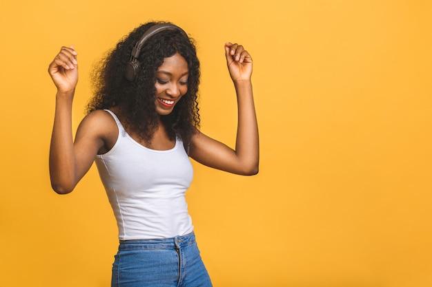 Inspirierte afroamerikanerin, die musik hört und mit geschlossenen augen tanzt