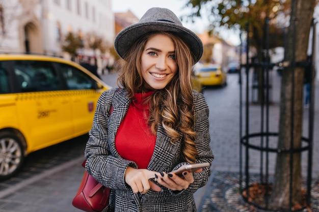 Inspirierte blauäugige geschäftsfrau, die mit telefon auf der straße posiert