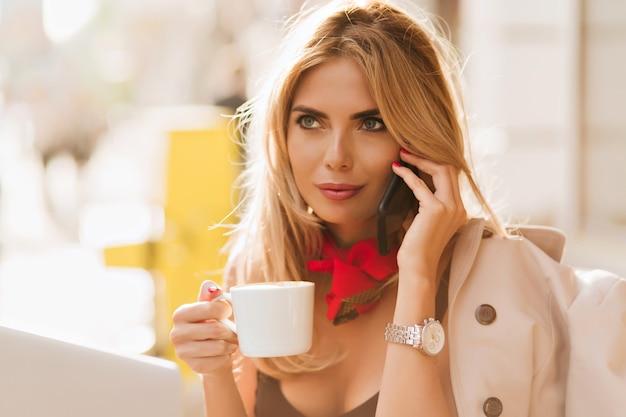 Inspirierte blonde frau mit rotem schal, die kaffee in der weißen tasse trinkt und gerüchte mit freund teilt