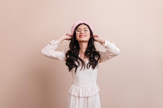 Inspirierte chinesische dame, die in baskenmütze aufwirft. vorderansicht des blithesome asiatischen mädchens im trendigen outfit.