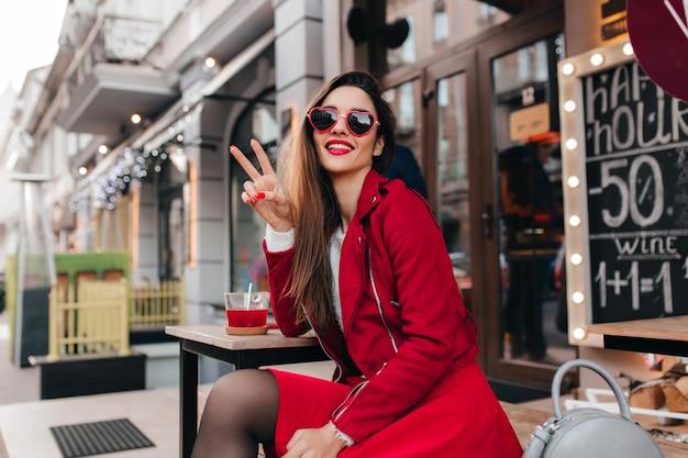 Inspirierte dame im trendigen roten rock, der friedenszeichen macht