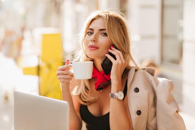 Inspirierte dame mit glattem haar, das zur kamera schaut und tasse tee und smartphone auf unscharfem hintergrund hält