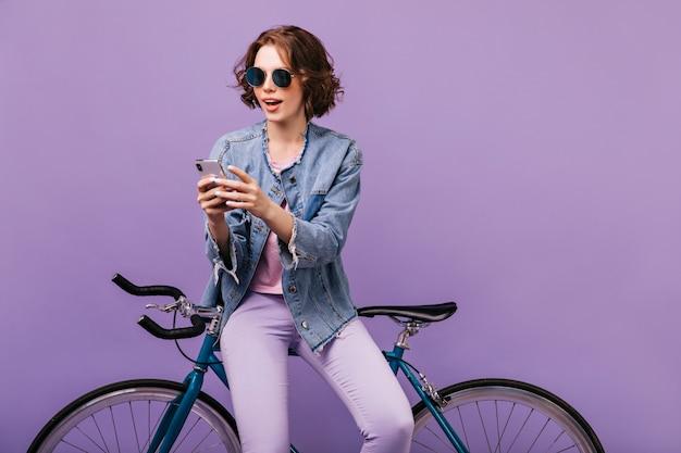 Inspirierte frau in der freizeitkleidung, die telefonbildschirm betrachtet. freudiges weißes mädchen in der dunklen sonnenbrille, die smartphone mit fahrrad verwendet.