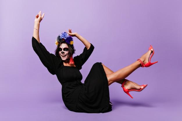 Inspirierte frau in roten schuhen mit hohen absätzen, die spaß an halloween haben. gut gelaunte dame im zombiekostüm, die auf dem boden sitzt und lacht.