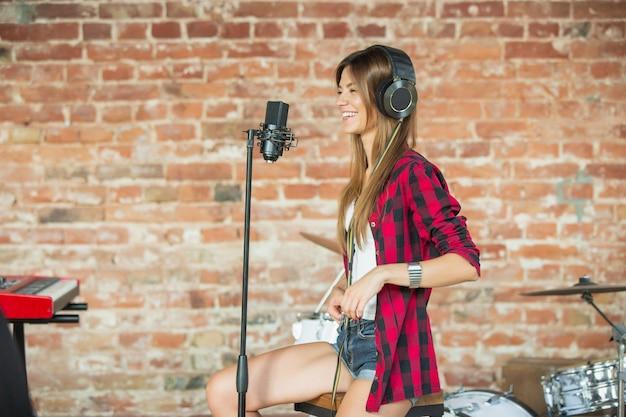 Inspirierte frau mit kopfhörern, die musik beim singen aufnimmt oder ein internet-tutorial macht