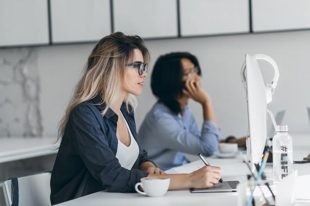 Inspirierte freiberufliche webdesignerin mit tablet und stift, die auf den bildschirm schaut, während ihre freundin telefoniert. asiatischer student, der smartphone hält und auf tastatur tippt und neben blondem mädchen sitzt.