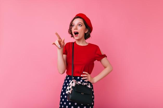 Inspirierte glamouröse frau in eleganter kleidung, die mit dem finger auf etwas interessantes zeigt. innenaufnahme des begeisterten kaukasischen mädchens in der französischen baskenmütze und in der roten bluse.