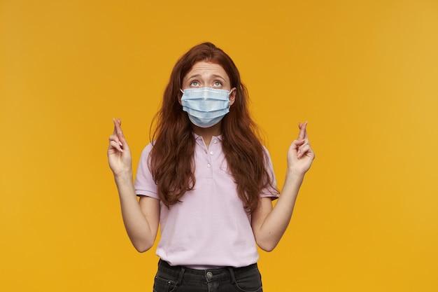 Inspirierte hübsche junge frau, die eine medizinische schutzmaske trägt, drückt die daumen und schaut über der gelben wand in den himmel