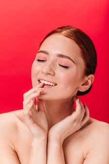 Inspirierte ingwerfrau, die lippen berührt. studioaufnahme des nackten weiblichen modells, das mit geschlossenen augen auf rotem hintergrund aufwirft.
