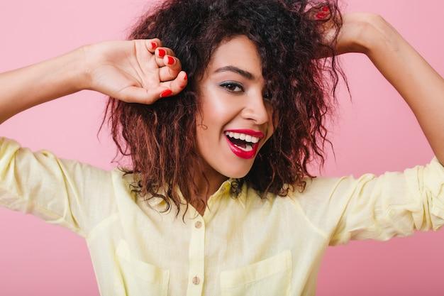 Inspirierte junge dame mit roter maniküre, die mit erhobenen händen und aufrichtigem lächeln aufwirft. elegante mulattin mit kurzer frisur, die glück ausdrückt.
