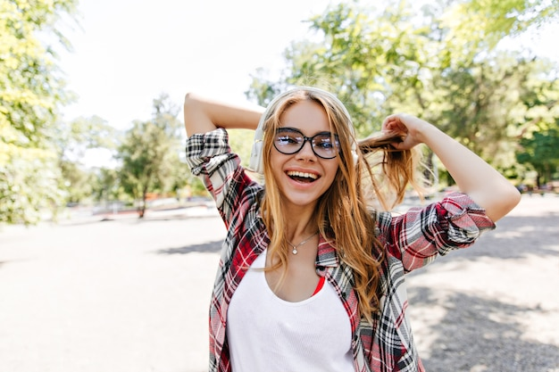Inspirierte junge frau, die im warmen frühlingstag lächelt. sommerporträt des interessierten blonden mädchens in den gläsern.